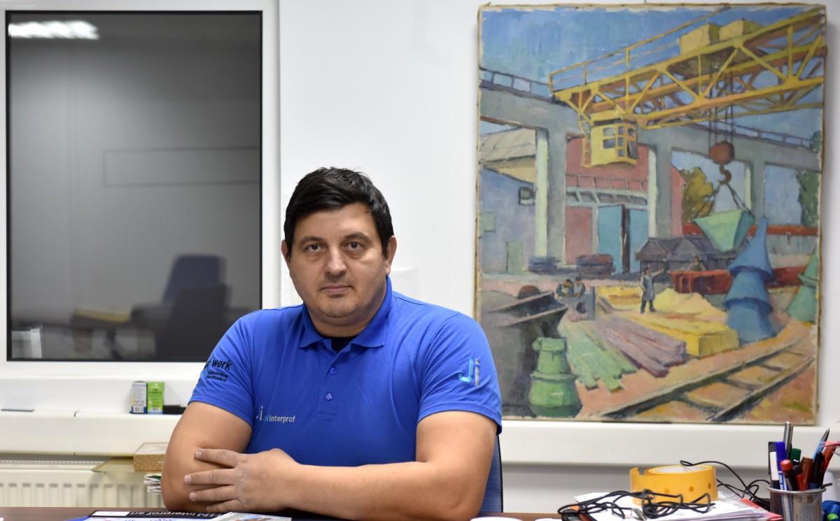 """În biroul fabricii sale, Stelian Ticușan are un tablou """"salvat"""" de la demolarea fabricii Balanța. Un tablou care surprindea activitatea fostei fabrici sibiene"""